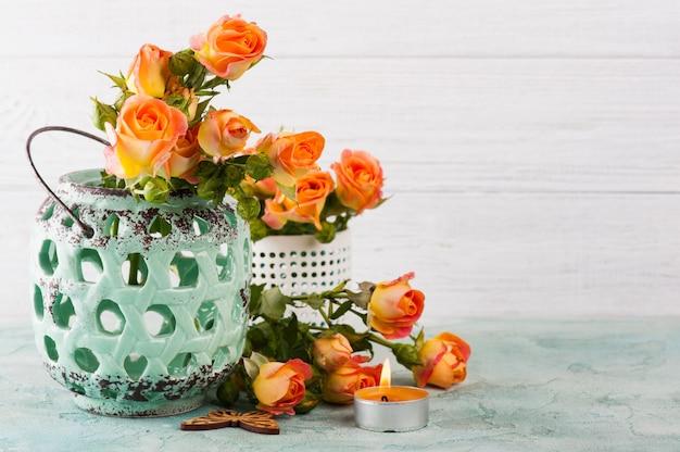 Flores de rosas alaranjadas frescas em vaso de hortelã e vela acesa