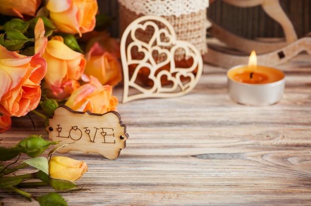 Flores de rosas alaranjadas frescas, garrafa de decoração de coração de madeira e vela acesa
