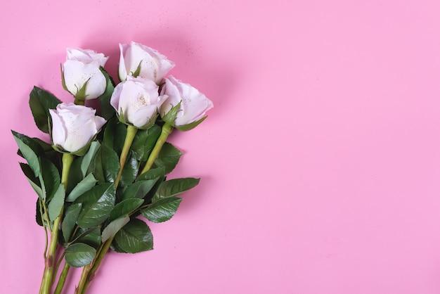 Flores de rosas cor de rosa com glitter dourados sobre um fundo rosa, plana leigos