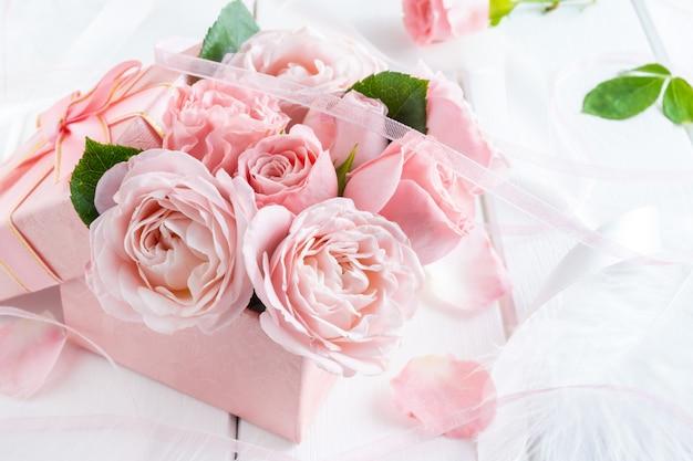 Flores de rosas cor de rosa em caixa de presente com fitas.