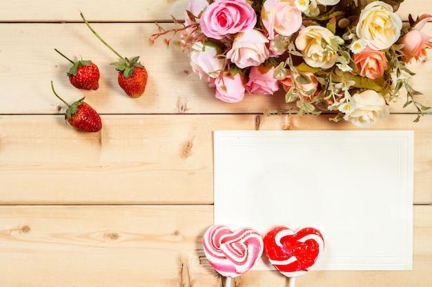 Flores de rosas de tom de cor pastel e tag vazia para o seu texto com doces de forma de coração com fundo de madeira