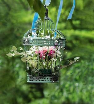 Flores de rosas e peônias em uma gaiola antiga vintage estão penduradas em uma árvore na composição florística do casamento.