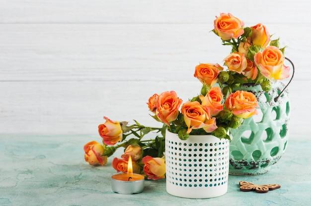 Flores de rosas laranja frescas em vaso de hortelã e vela acesa