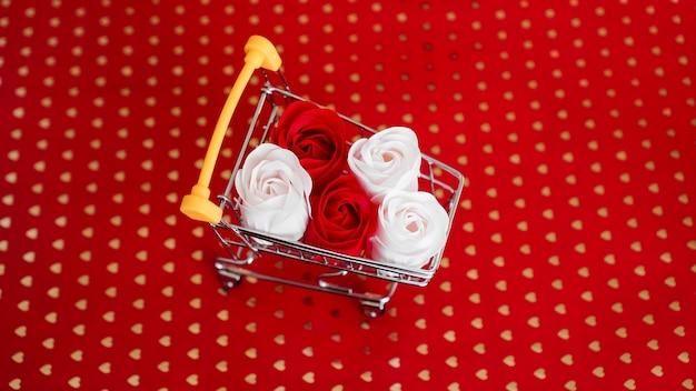 Flores de rosas vermelhas e brancas no carrinho de compras em fundo vermelho. férias de compras para o conceito de amor do dia dos namorados