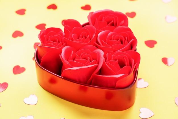 Flores de rosas vermelhas em forma de um coração em um fundo amarelo. o conceito de dia dos namorados, romance de casamento. copie o espaço.