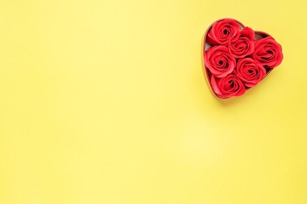 Flores de rosas vermelhas em forma de um coração em um fundo amarelo. o conceito de dia dos namorados, romance de casamento. flat lay copie o espaço.
