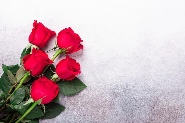 Flores de rosas vermelhas em fundo de pedra. cartão de dia dos namorados. vista do topo. copie o espaço