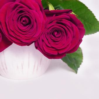 Flores de rosas vermelhas em vaso de cerâmico branco. fundo florido com espaço de cópia. foco seletivo.