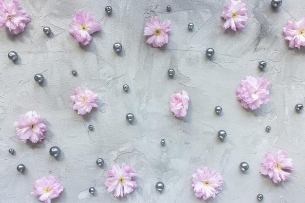 Flores de sakura rosa e pérolas em fundo cinza
