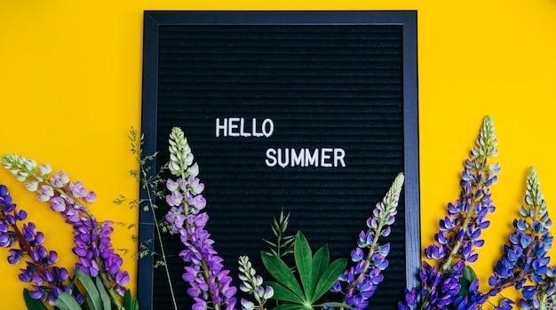 Flores de tremoço e uma placa com as palavras