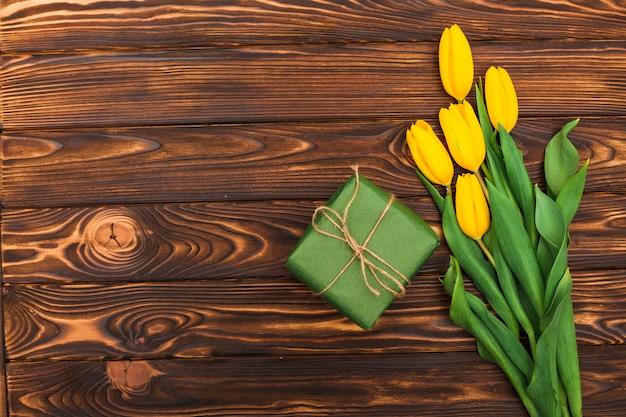 Flores de tulipa amarela com caixa de presente na mesa