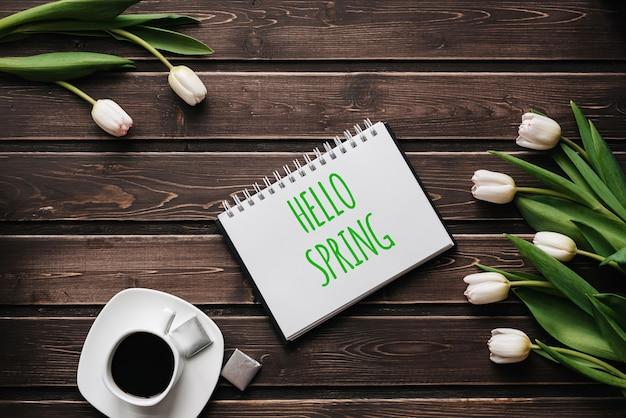 Flores de tulipa branca com uma xícara de café em uma mesa de madeira. cartão com letras olá primavera