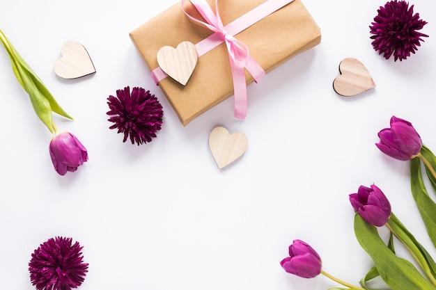 Flores de tulipa com caixa de presente e corações de madeira