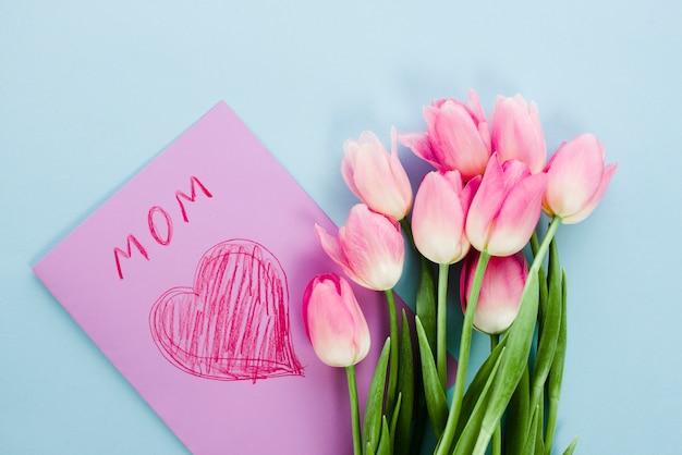 Flores de tulipa com cartão com inscrição de mãe