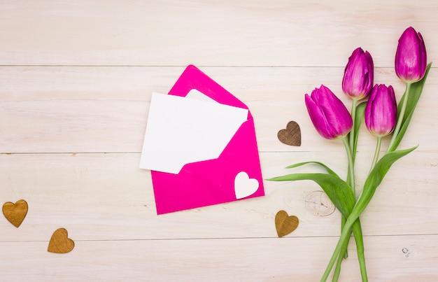Flores de tulipa com papel em branco no envelope