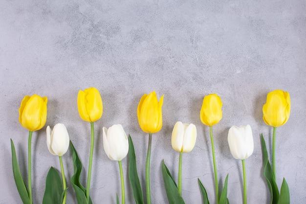 Flores de tulipas brancas e amarelas na superfície cinza