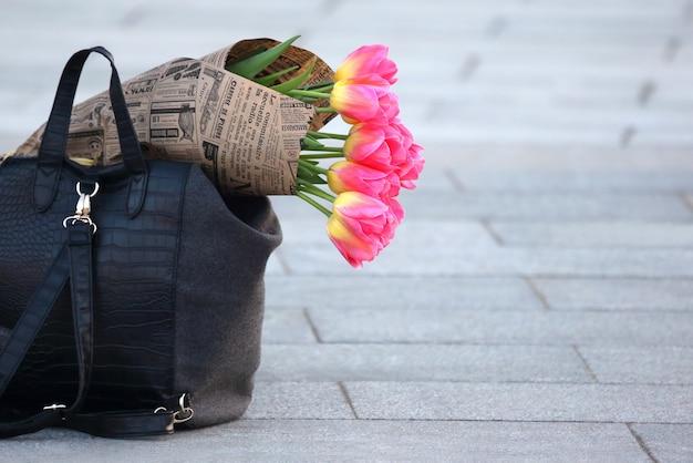 Flores de tulipas embrulhadas em jornal na bolsa feminina