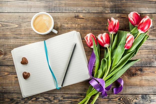 Flores de tulipas primavera fresca com bloco de notas, corações de chocolate doces e caneca de café
