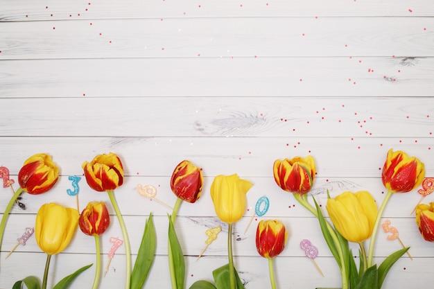Flores de tulipas vermelhas, amarelas, vela e confetes em fundo de madeira.