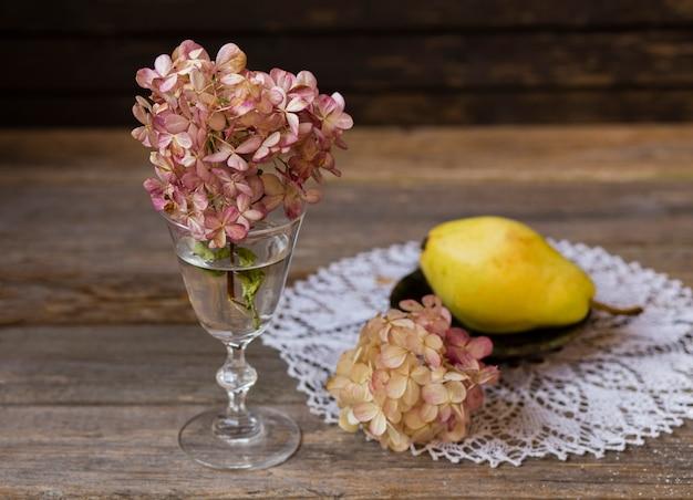Flores de uma rosa hortênsia ficar em uma mesa de madeira em um velho vidro transparente, uma toalha de mesa landim, um prato de barro com uma pêra amarela