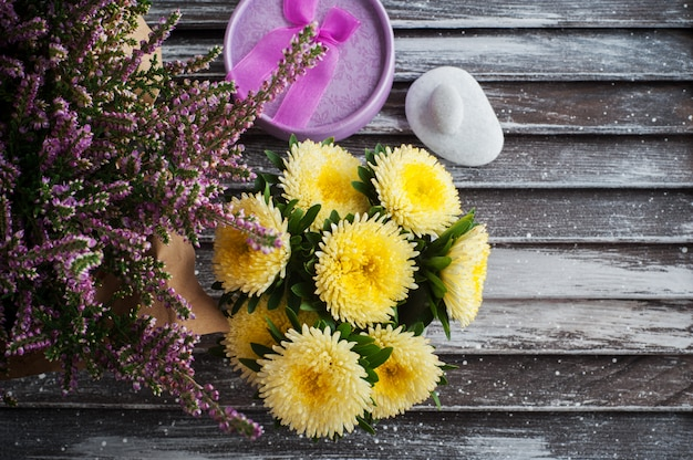 Flores de urze, margaridas amarelas e caixa de presente