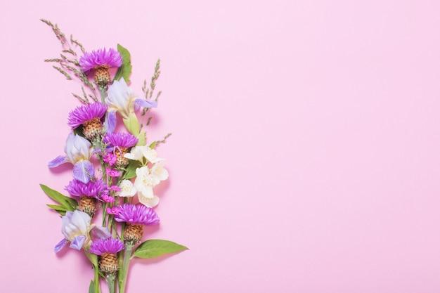 Flores de verão na superfície de papel rosa