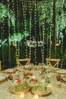 Flores decorando as peças centrais com talheres de luxo nas mesas de um salão de festas.