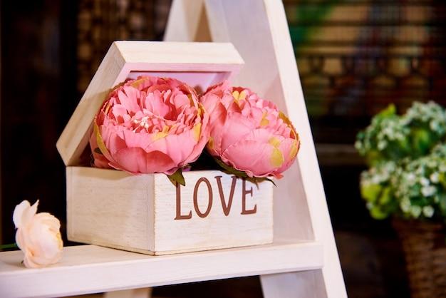 Flores decorativas em caixa de madeira na prateleira.