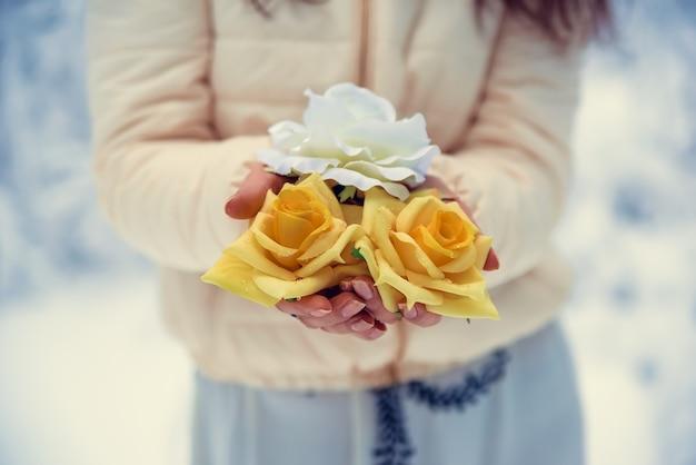 Flores delicadas nas mãos de uma menina no inverno.