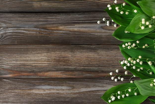 Flores do lírio do vale em madeira rústica. vista do topo. configuração plana
