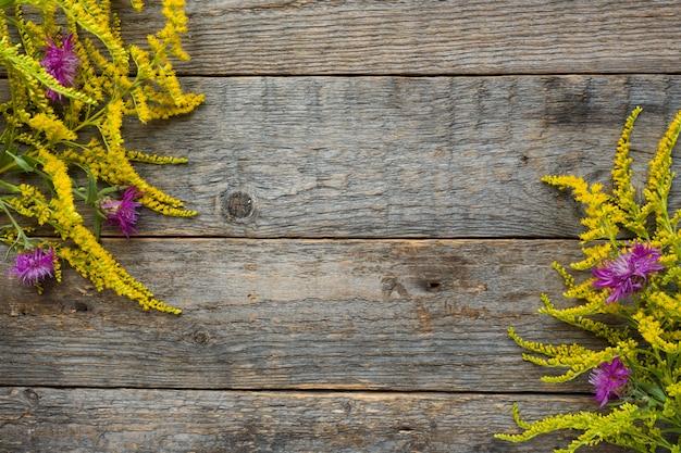 Flores do outono no fundo rústico de madeira. espaço da cópia