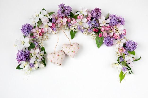 Flores do pássaro árvore de cereja, lilás e macieiras forrado com um arco e dois corações de tecido