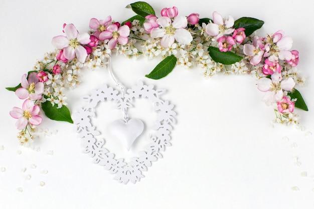 Flores do pássaro cereja e a macieira são forradas com um arco e um coração de rendilhado branco