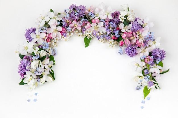 Flores do pássaro cereja, lilás, esqueça-me nots e macieiras são forradas com um arco