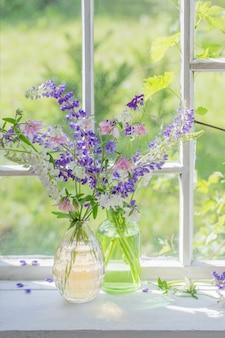 Flores do verão em um vaso no peitoril da janela na luz solar