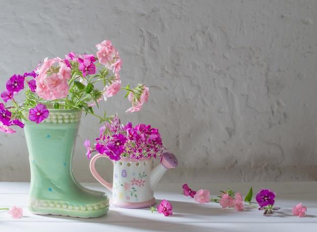 Flores do verão na bota cerâmica na superfície branca