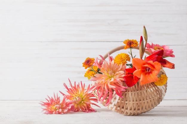 Flores do verão na cesta na mesa de madeira