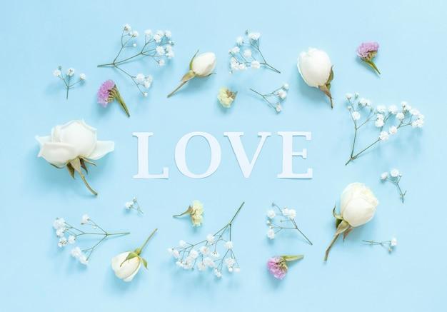 Flores e a palavra amor em uma vista superior de fundo azul claro