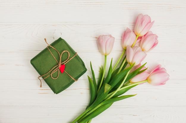 Flores e caixa de presente na mesa de madeira branca