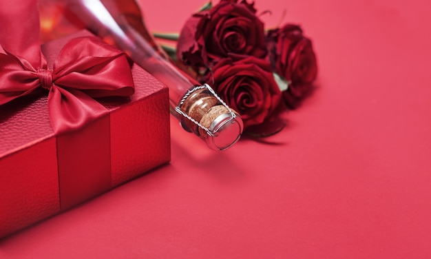 Flores e caixas de presentes em uma garrafa de champanhe vermelha e copos