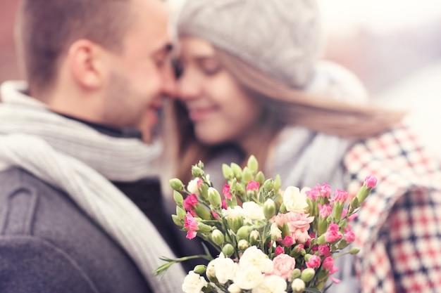 Flores e casal se beijando ao fundo