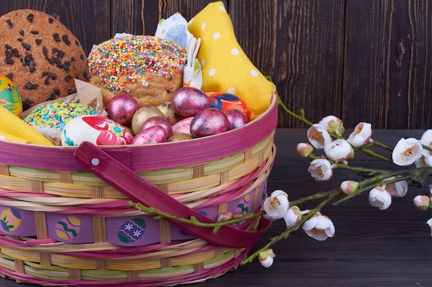 Flores e comida tradicional de páscoa de close-up. bolos com ovos e cookines. fundo de madeira rústico escuro.