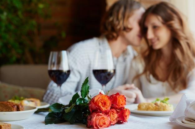 Flores e copos de vinho com fundo borrado