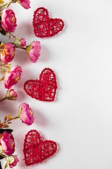 Flores e corações vermelhos em um fundo branco para o dia dos namorados. quadro de corações e flores sobre fundo branco, lugar para texto. design para o dia dos namorados, foto vertical