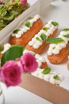 Flores e éclairs decorados com creme e hortelã em uma mesa branca. sobremesa para um encontro romântico. bolos para o feriado.