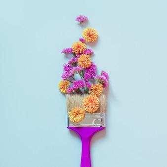 Flores e escova de pintura amarelas e cor-de-rosa no azul.