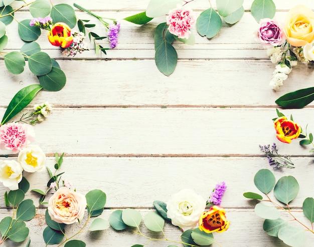 Flores e folhas de moldura floral no espaço de design de madeira