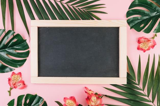 Flores e folhas de palmeira em torno do quadro-negro
