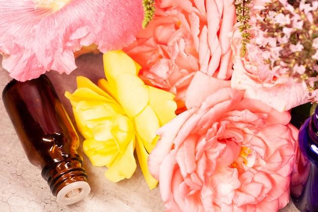Flores e frascos de óleos essenciais para aromaterapia