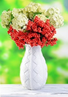 Flores e frutas em um vaso, na mesa de madeira, no fundo brilhante